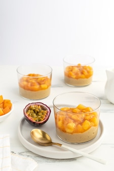 Caramel panna cotta, custard pudding with peach and passion fruit, white table, copy space
