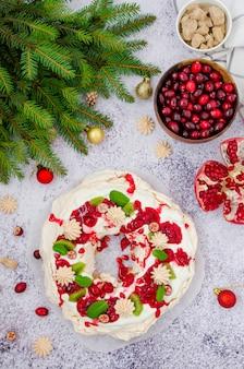 Caramel pavlova christmas wreath with cherry sauce, pomegranate, cranberries and kiwi on a light stone background
