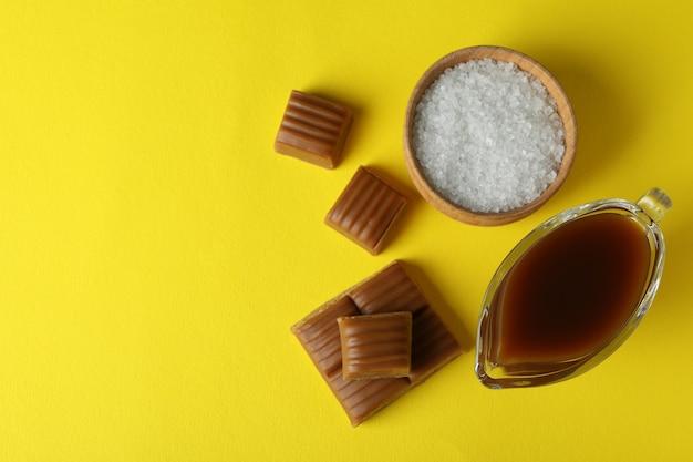 Кусочки карамели, соус и миска соли на желтом фоне