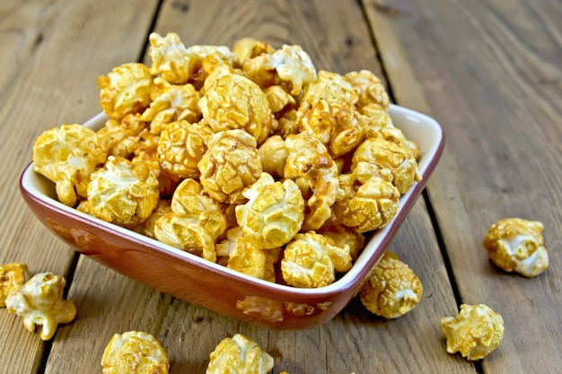 Caramel popcorn in a clay bowl on a wooden boards background