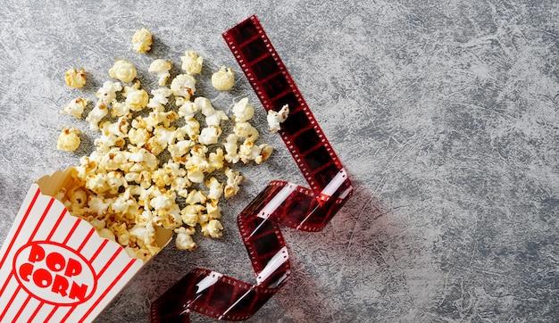 로프트 배경 35mm 필름에 있는 종이컵에 있는 카라멜 팝콘은 평평한 영화관을 깔았습니다
