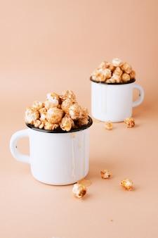 Карамельный попкорн в винтажных белых металлических чашках на коричневой стене