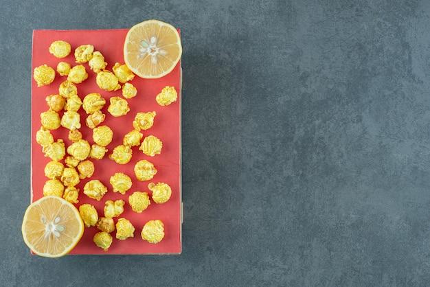 대리석 배경에 얇게 썬 레몬 조각 옆에 있는 나무 판자에 있는 카라멜 팝콘. 고품질 사진