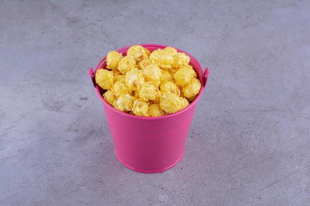 Карамельный попкорн подается в небольшом ведерке на мраморном фоне. фото высокого качества