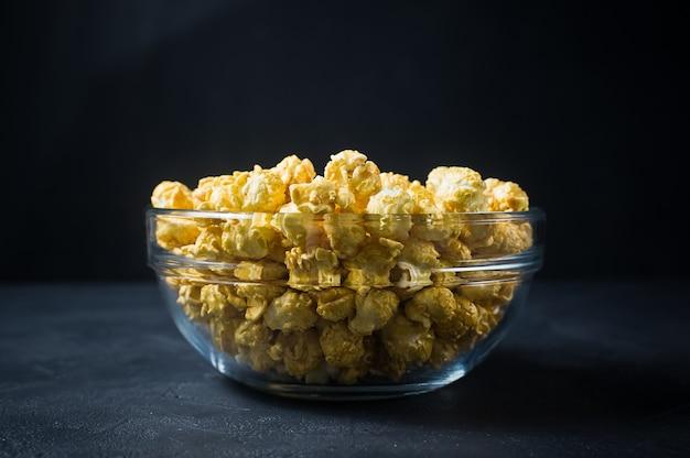 Caramel popcorn in a transparent bowl.