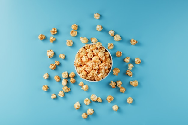 Caramel popcorn in a white glass cup with scissors on a blue surface. a delicious catch for filming movies, tv series, cartoons. free legal, crimes.
