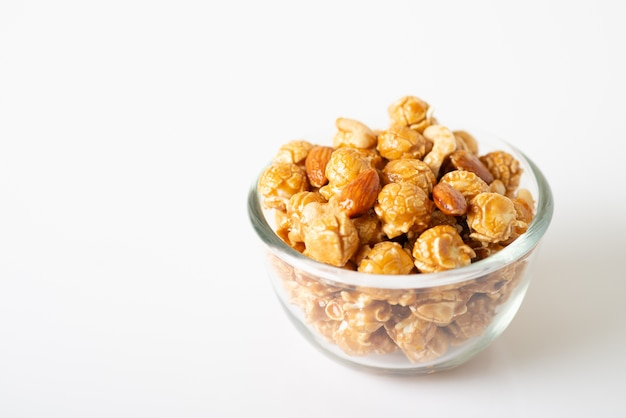 Caramel popcorn with cashew nuts and almonds in a white background