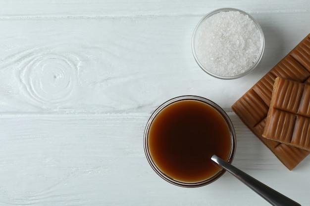 Карамельный соус, батончик и соль на белом деревянном фоне
