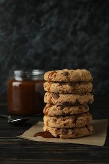 카라멜, 숟가락 및 나무 테이블에 쿠키