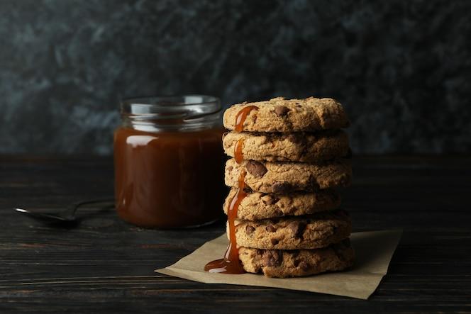 caramello, cucchiaio e biscotti sulla tavola di legno