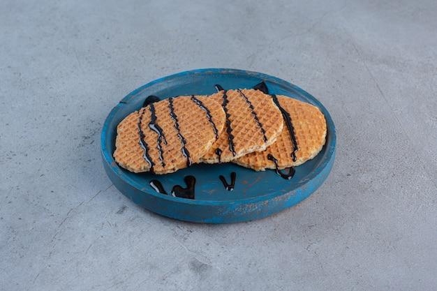 Cialde al caramello decorate con salsa di cioccolato su piatto blu.