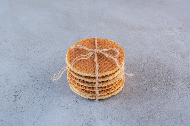 Caramel waffles tied up with jute bow isolated on a stone surface