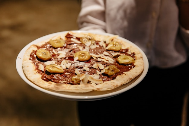 Caramelized banana nutella pizza. ingredients are pizza dough