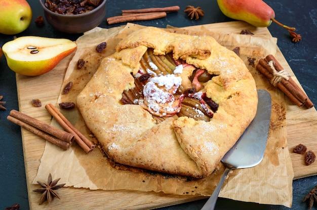 검정색 배경에 계피와 건포도를 곁들인 카라멜화된 배 파이. 맛있고 간단한 디저트.