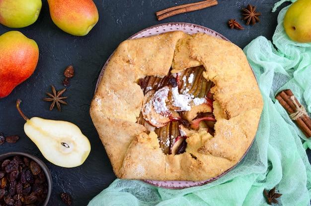 검정색 배경에 계피와 건포도를 곁들인 카라멜화된 배 파이