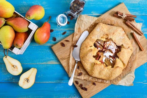 푸른 나무 배경에 계피와 건포도를 곁들인 카라멜화된 배 파이. 맛있고 간단한 디저트. 소박한 스타일. 평면도.