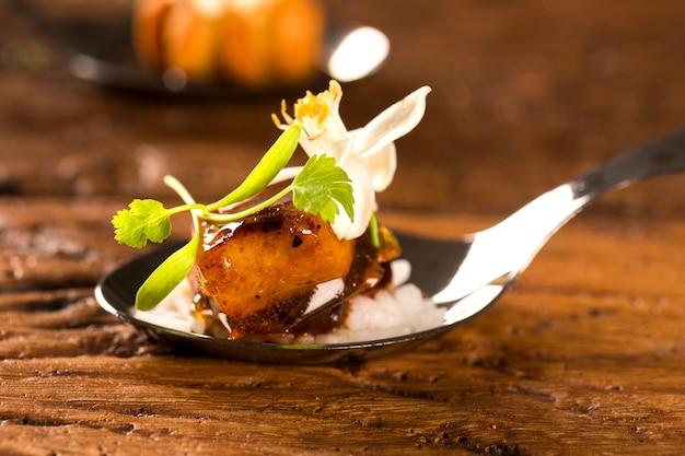 Карамелизированная свинина с жасминовым рисом и красным карри в ложке. вкус гастрономической еды руками
