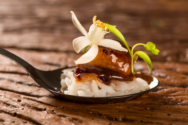 Caramelized pork accompanied by jasmine rice and red curry in a spoon. taste gastronomy fingerfood