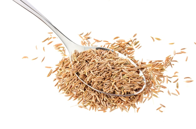 Caraway in spoon on white surface