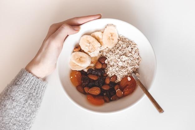 炭水化物の健康的な朝食。白い皿にドライフルーツとオートミール。上から見る