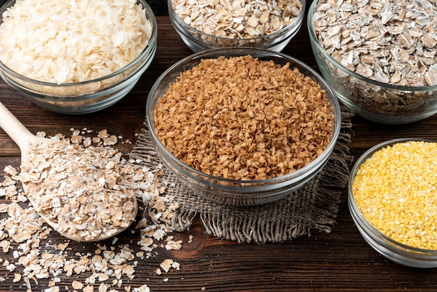 Carbohydrates. various grain flakes in bowls on dark wooden table.