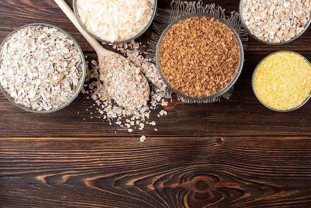 炭水化物。暗い木製のテーブルのボウルにさまざまな穀物フレーク。