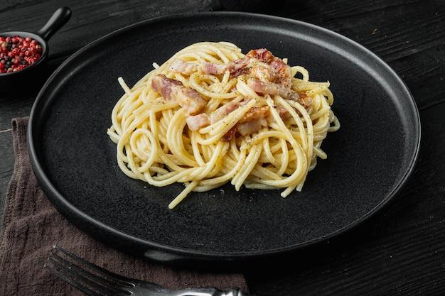Блюдо для пасты карбонара. традиционная римская кухня. набор итальянской кухни, на черном деревянном фоне