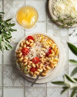 Паста карбонара, макароны и сыр на тарелке на плиточном столе с помидорами, пармезаном, тимьяном на тарелке, апельсиновым соком в стакане. сервировка стола с растениями шалфея. тарелки, вилка и стакан на кафельном столе