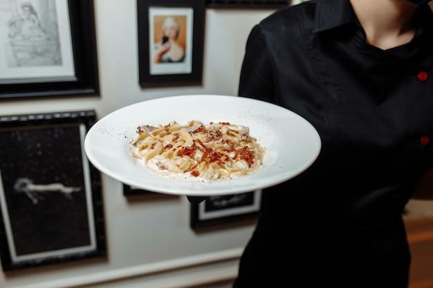 白い皿にチーズがたっぷり入ったカルボナーラパスタ。カルボナーラパスタのプレートを持ったウェイター。