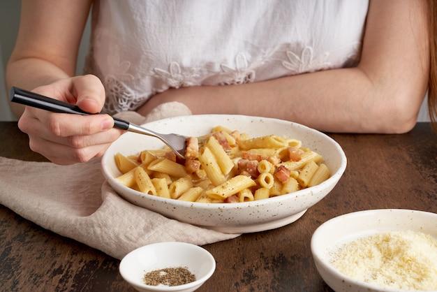 カルボナーラパスタ。女性はテーブルに座って、パンチェッタとパスタペンネを食べる、