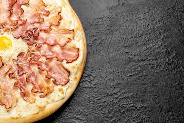 Carbonara pizza on a black background, cream-based with mozzarella