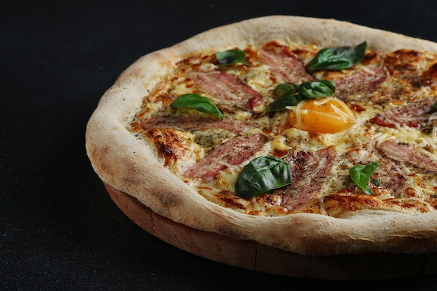 Carbonara pizza with bacon and egg on dark background