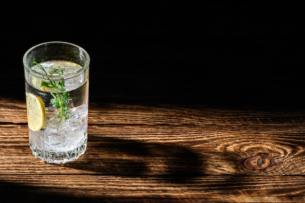 Carbonated cold water with ice and lemon dropping long shadow on wooden table