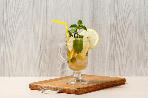 Газированный лимонад с дольками лимона и мятой на деревянной разделочной доске, холодный напиток для жаркого летнего дня