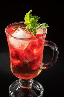 Газированный лимонад с кусочками клубники и мятой на черном фоне. холодный напиток для жаркого летнего дня