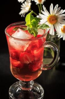 Газированный лимонад с кусочками клубники и мятой с цветками ромашки на черном фоне. холодный напиток для жаркого летнего дня