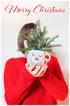 赤いセーターを着た女の子のカードは、雪だるまの顔のマグカップを持っており、顔の前にモミの枝があり、メリークリスマスの碑文があります。