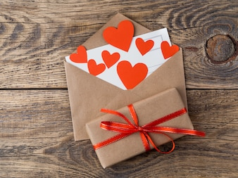 Card and red hearts in open envelope from brown Kraft paper. Greetings with Valentine's da