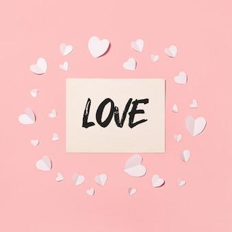 ピンクの背景にカードとホワイトペーパーのハート。作曲バレンタインデー。バナー。フラットレイ、上面図。