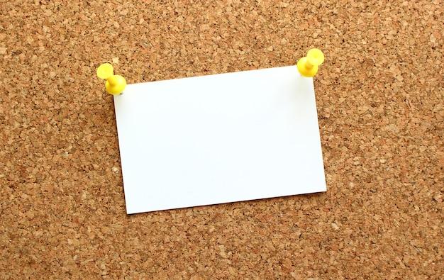 Карточка, прикрепленная к пробковой доске с напоминанием кнопки на доске офиса