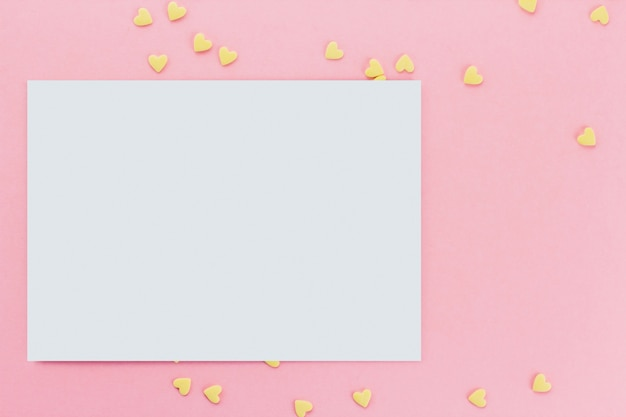 Card on a background of heart-shaped confectionery confetti on a pink background copy space. yellow hearts