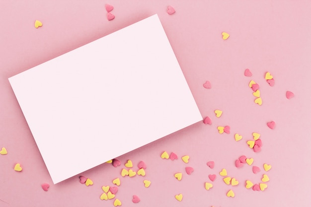 Card on a background of heart-shaped confectionery confetti on a pink background copy space. yellow and pink hearts