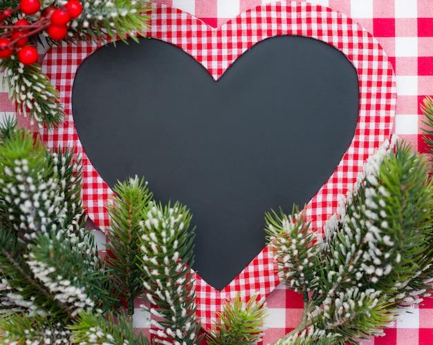 赤いギンガムチェックのテーブルクロス冬の休日にクリスマスツリーの枝とハートの形で空白のカード