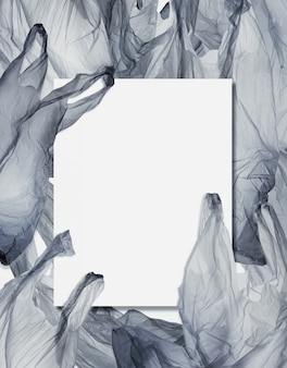 A card blank on pile of plastic bags.environmentalism and plastic awareness concept background.