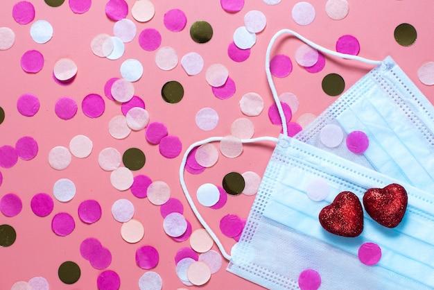 Открытка на день святого валентина. на розовом фоне медицинские маски и два красных сердца. смешные поздравления. плоская планировка, вид сверху.