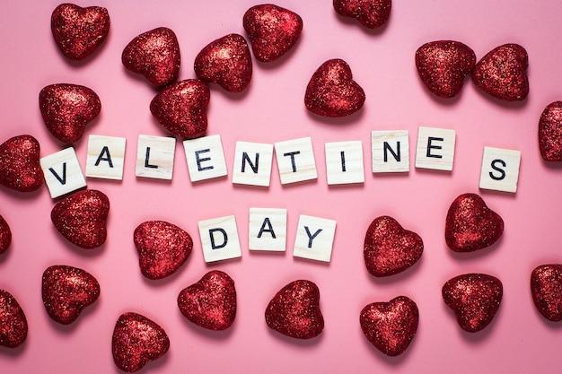 Открытка на день святого валентина. на розовом фоне деревянные буквы выложены любовью. смешные поздравления. плоская планировка, вид сверху. красные блестящие сердца.