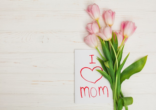 Card i love mom and flowers placed on white wood table