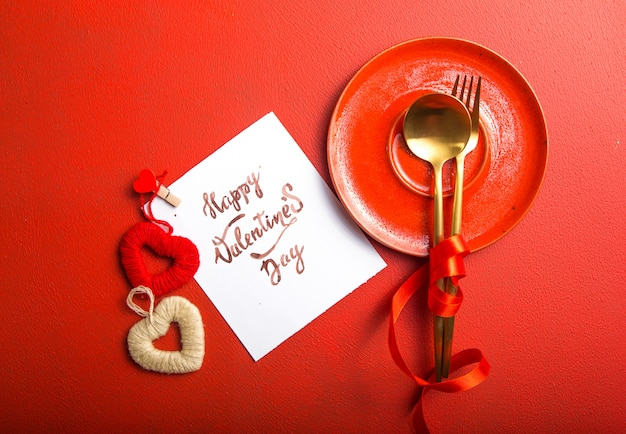 Card message with happy valentines day, golden cutlery and heart toys
