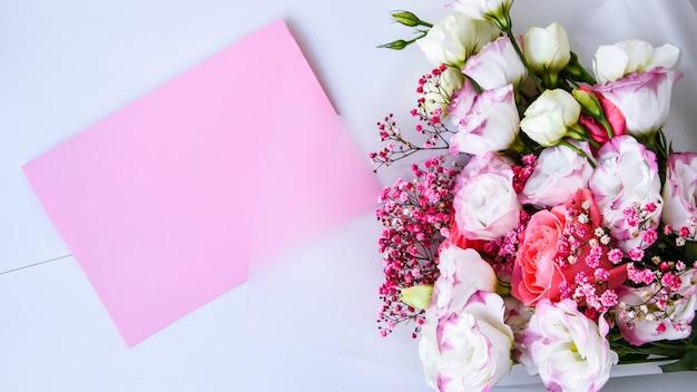 繊細な花束のカードモックアップ。花の背景。上面図フラットレイホリデーカード3月8日、幸せなバレンタインデー、母の日のコンセプト。テキスト用のスペースをコピーします。ホリデーグリーティングカード