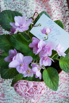 Card for mother's day with an inscription in a flower pot with a violet
